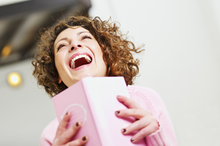 woman laughing with a book in hand